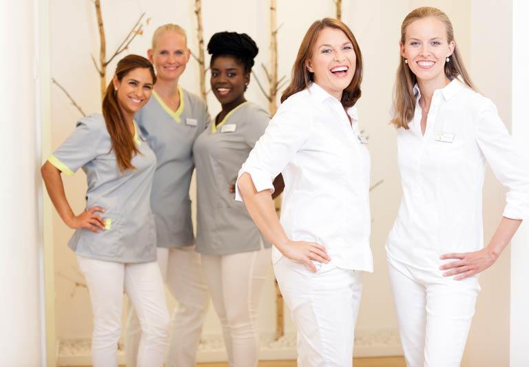 Dr. Beate Jürgens und Dr. Susanne Hörmann vor ihren Mitarbeiterinnen in der Zahnarztpraxis in Düsseldorf Oberkassel
